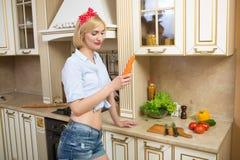 Fille tenant une grande carotte dans la cuisine Photo stock
