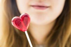 Fille tenant une lucette rouge sous forme de coeur Photographie stock libre de droits