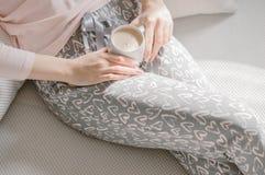 Fille tenant une tasse de café dans des mains sur des jambes pendant le matin images libres de droits