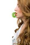 Fille tenant une tranche de kiwi avec les lèvres Image libre de droits