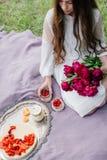 Fille tendre avec dessus un pique-nique avec des gâteaux au fromage et des pivoines Photos libres de droits