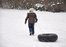 Fille tirant le tube sledding vers le haut la côte photographie stock libre de droits