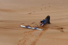Fille tombant de son panneau de sable Photo stock