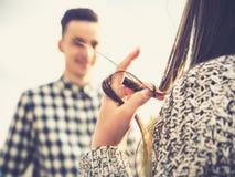 Fille touchant ses cheveux tout en flirtant avec un type Photo libre de droits