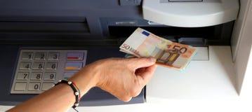 Fille tout en retirant 50 billets de banque d'euros d'une atmosphère Photos stock
