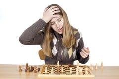 Fille très déçue de jeunes giflant la main sur la tête pour dire Duh, regrettant pour l'erreur elle a fait pendant le jeu d'échec Photo libre de droits