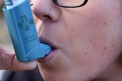 Fille traitant l'asthme avec l'inhalateur de cannabis image libre de droits