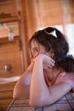 Fille tranquille se penchant sur la table Images libres de droits