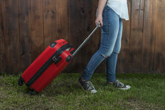 Fille transportant une valise rouge Image stock
