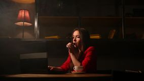 Fille travaillant avec du café potable d'ordinateur portable fumant une cigarette électronique Travail à distance dans un café clips vidéos
