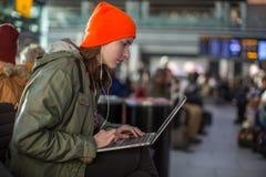 Fille travaillant avec l'ordinateur portable dans le hall de attente d'aéroport Images stock