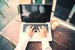 Fille travaillant avec l'ordinateur portable dans un café avec la tasse de café Photo stock