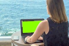 Fille travaillant avec un carnet sur la terrasse d'un hôtel regardant la mer vert principal de chroma images libres de droits