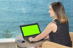 Fille travaillant avec un carnet sur la terrasse d'un hôtel regardant la mer vert principal de chroma photographie stock libre de droits