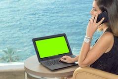 Fille travaillant avec un carnet sur la terrasse d'un hôtel regardant la mer vert principal de chroma images stock