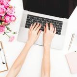Fille travaillant sur l'ordinateur portatif Espace de travail avec les mains, l'ordinateur portable, le bouquet de roses et le jo Photos libres de droits