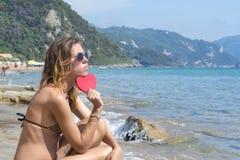 Fille triste avec le coeur rouge sur le bord de la mer Photo stock