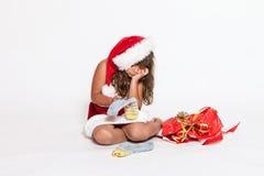 Fille triste dans le costume de Santa Claus avec le cadeau inadéquat photos stock