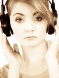 Fille triste de femme dans la musique de écoute de grands écouteurs Images stock
