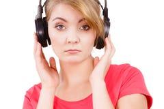 Fille triste de femme dans la musique de écoute de grands écouteurs Photo stock
