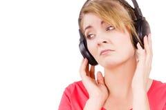 Fille triste de femme dans la musique de écoute de grands écouteurs Photographie stock libre de droits
