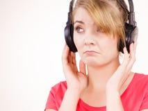 Fille triste de femme dans la musique de écoute de grands écouteurs Images libres de droits