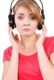 Fille triste de femme dans la musique de écoute de grands écouteurs Photos libres de droits
