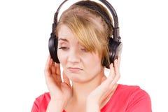 Fille triste de femme dans la musique de écoute de grands écouteurs Image stock