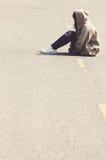 Fille triste et navrée s'asseyant sur le vintage de route Photographie stock libre de droits