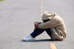 Fille triste et nerveuse s'asseyant sur la route Photographie stock