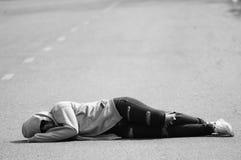 Fille triste et seule dormant sur la route Photos stock