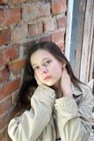 Fille triste près de mur de briques Photographie stock