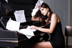 Fille triste près de piano Image libre de droits