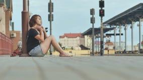 Fille triste s'asseyant sur les tuiles de la gare ferroviaire dans les écouteurs clips vidéos