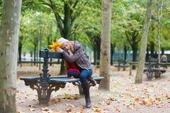 Fille triste s'asseyant sur un banc en parc Images libres de droits