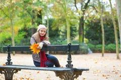 Fille triste s'asseyant sur un banc en parc Images stock