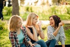 Fille trois hippie mignonne s'asseyant dehors, meilleurs amis ayant l'amusement et rire Image libre de droits