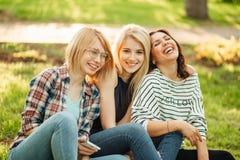 Fille trois hippie mignonne s'asseyant dehors, meilleurs amis ayant l'amusement et rire Images libres de droits