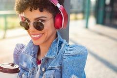 Fille urbaine africaine avec des écouteurs images stock