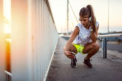 Fille urbaine de sport avec des écouteurs se reposant sur le pont dans le coucher du soleil photo libre de droits