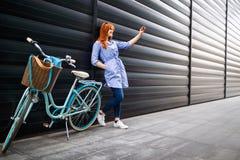 Fille urbaine prenant le selfie dans la ville près du vélo photographie stock libre de droits