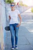 Fille utilisant le T-shirt blanc vide, jeans posant contre le mur rugueux de rue photographie stock libre de droits