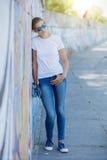 Fille utilisant le T-shirt blanc vide, jeans posant contre le mur rugueux de rue images stock