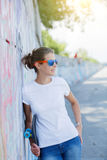 Fille utilisant le T-shirt blanc vide, jeans posant contre le mur rugueux de rue photos libres de droits