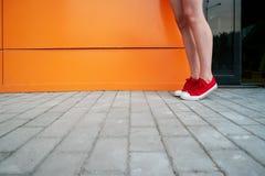 Fille utilisant les espadrilles à la mode Les chaussures se ferment vers le haut de la pousse devant le mur orange Photographie stock