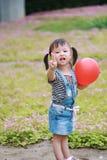 Fille vilaine mignonne d'enfant d'Aisa la belle avec le jeu de pose de V avec le ballon ont l'amusement extérieur dans l'enfance  Photographie stock