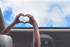 Fille voyageant par la voiture et les prises ses mains sous forme de coeur de trappe ouverte d'un véhicule photos stock