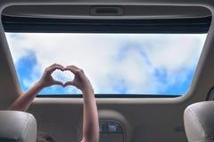 Fille voyageant par la voiture et les prises ses mains sous forme de coeur de trappe ouverte d'un v?hicule photos libres de droits