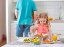 Fille withpretty de père heureux prenant le petit déjeuner d'amusement Image libre de droits