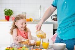 Fille withpretty de père heureux prenant le petit déjeuner d'amusement Photo stock